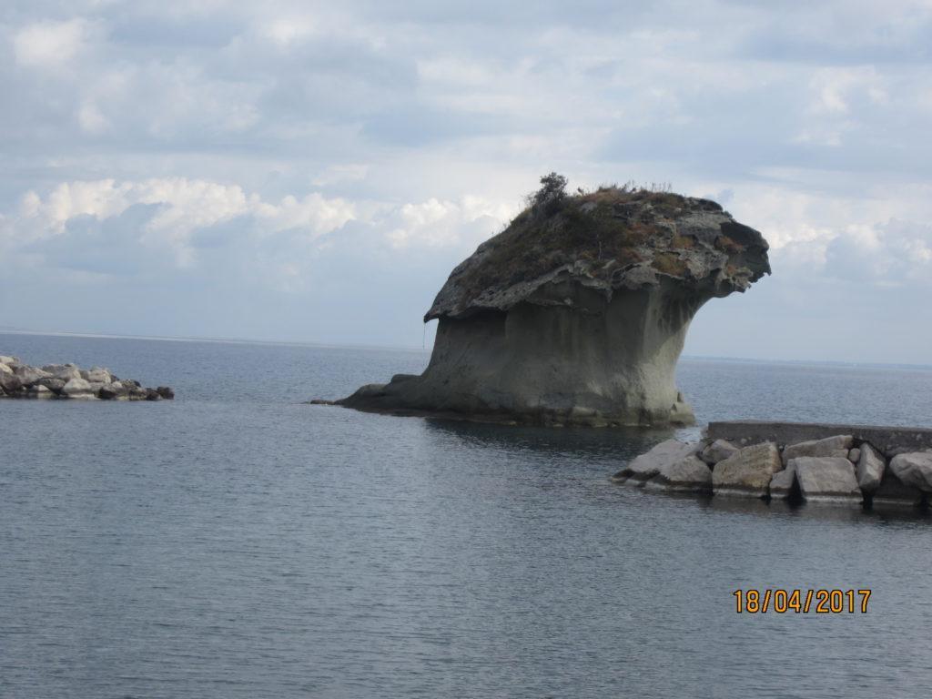 Одинокая скала в море в виде гриба.